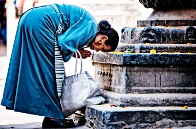 Woman in prayer position in Boudanath